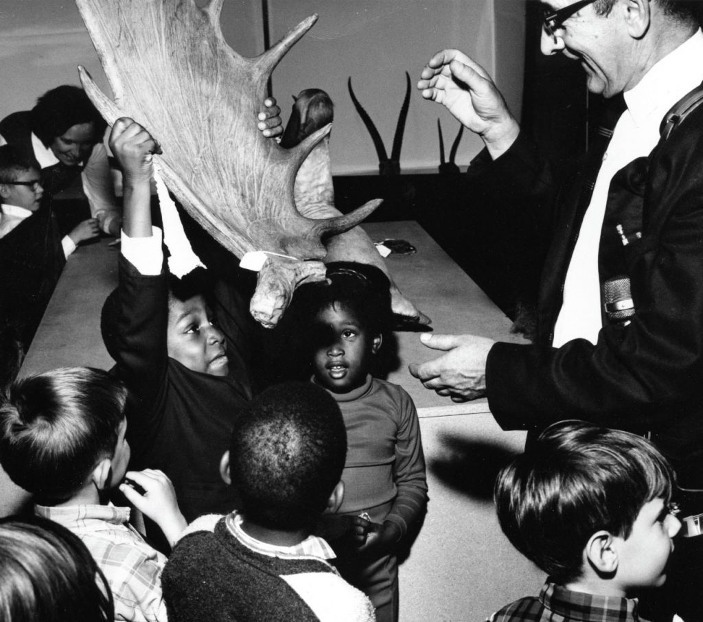 Lab founder with young students in the 1970s, one is proudly holding up a moose antler
