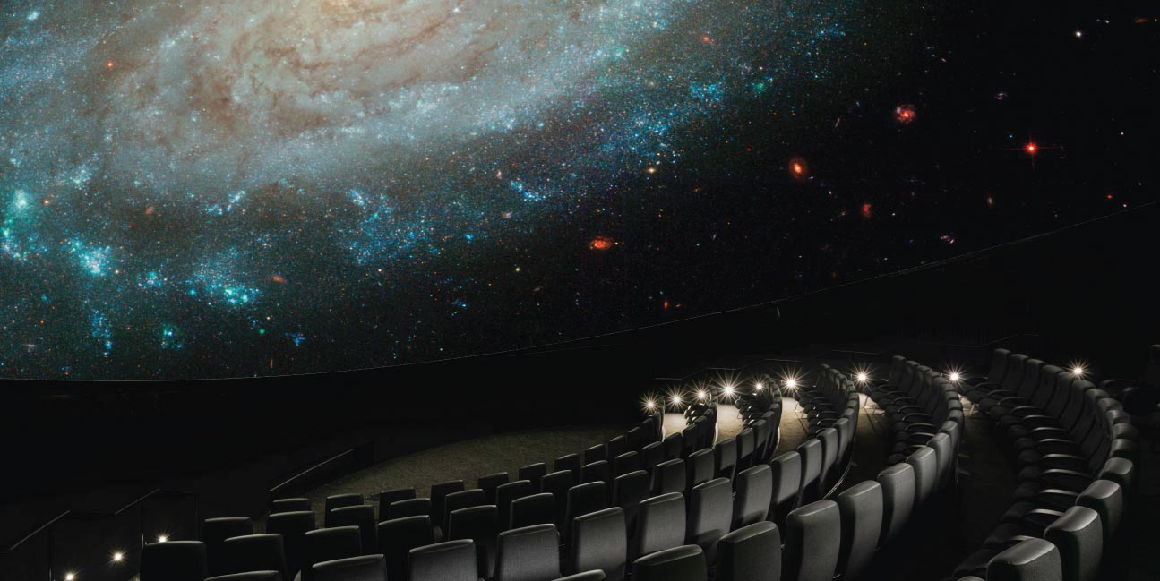 A galaxy appears on dome screen inside the planetarium theater.