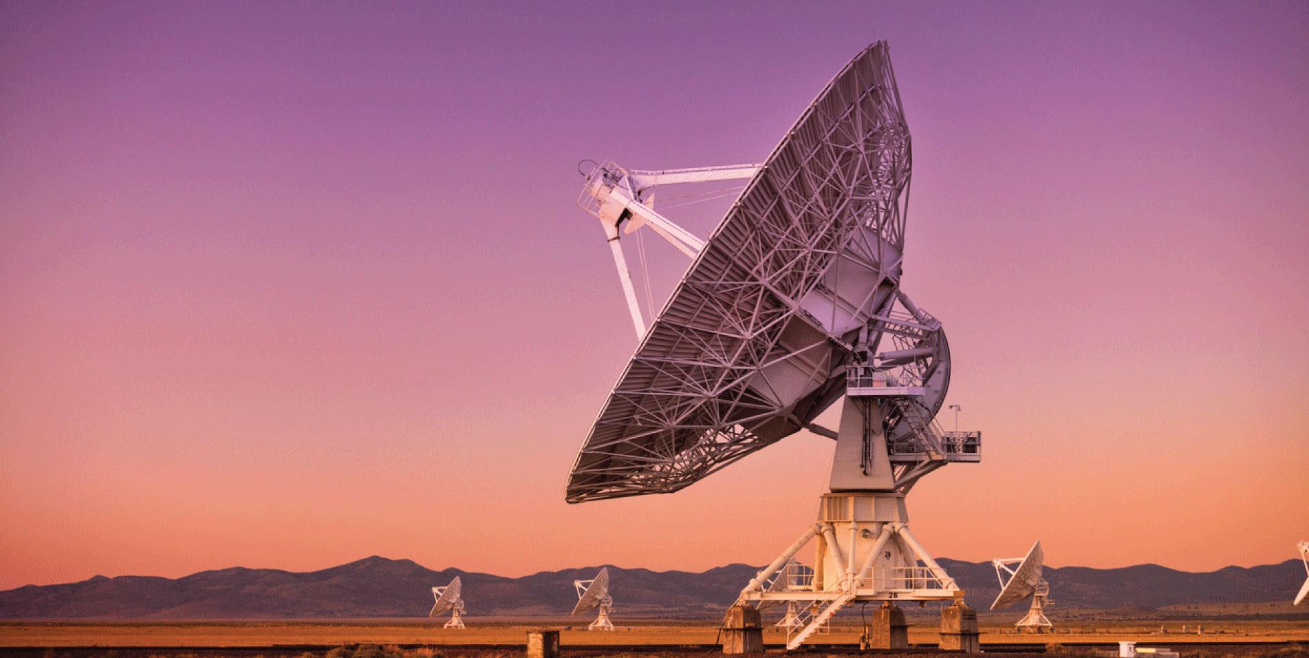 Array of large powered radio telescopes at sunset.