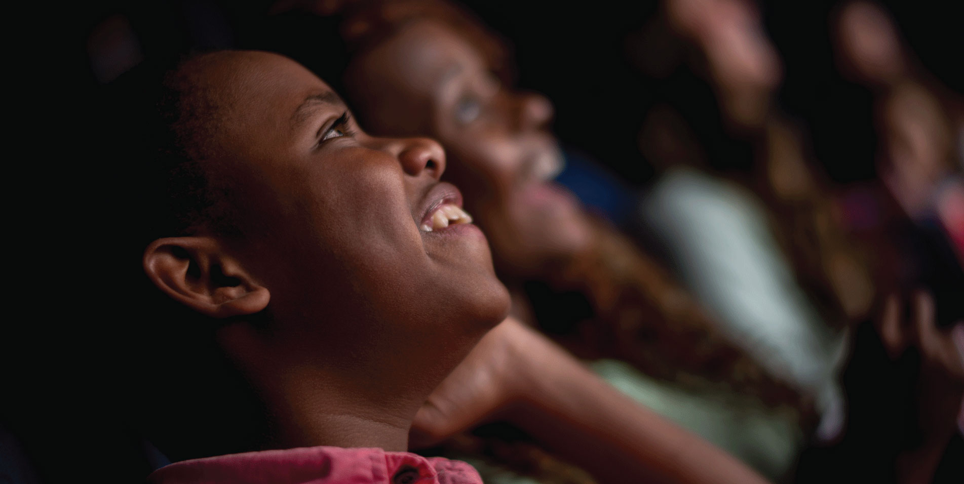 Theater audience whose faces are lite by the screen