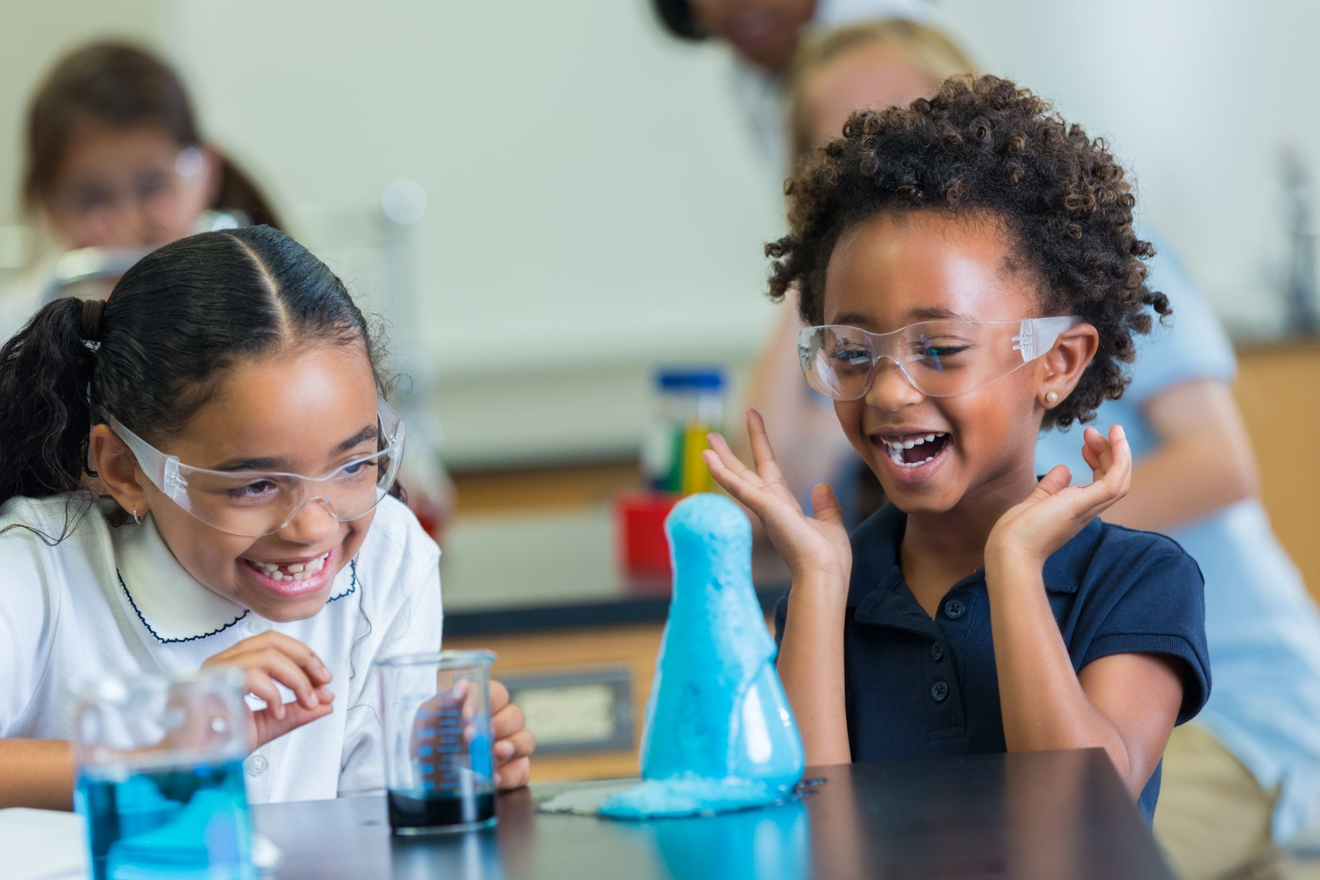 Cute elementary STEM schoolgirls giggle as foam overflows beaker during science experiment. They are wearing protective glasses and school uniforms.