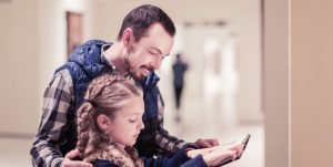 Father and daughter read information at a museum.