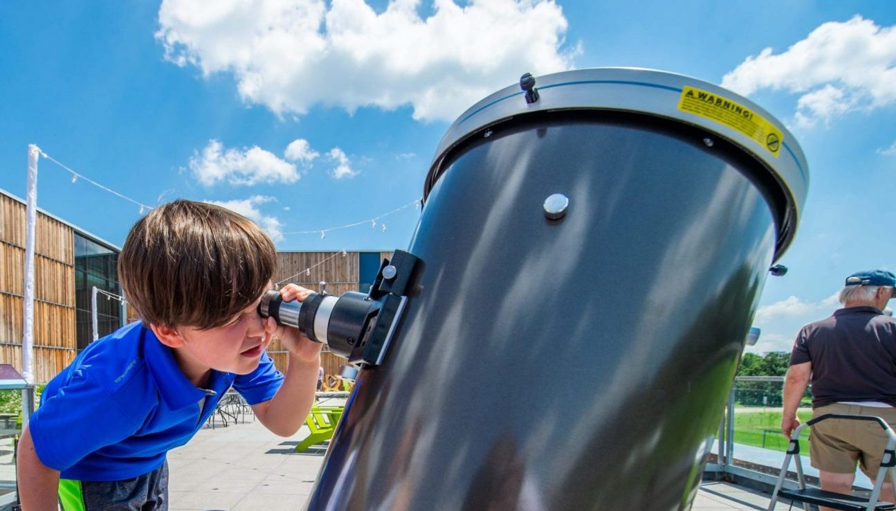 Young boy using specially outfitted telescope to safely view the Sun.