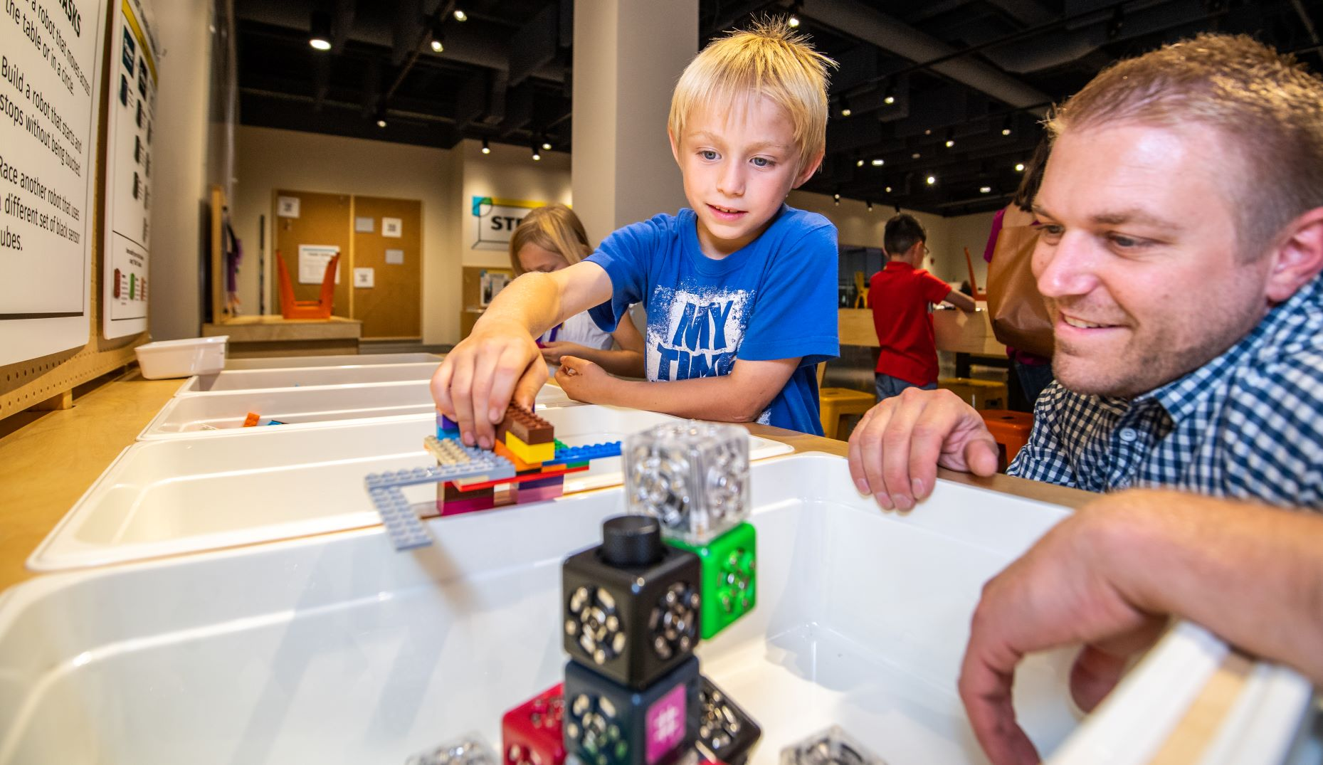 Boy and Father playing with legos and robot cubes