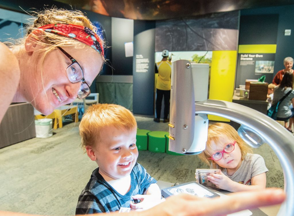 Mother and children look at specimens with a microEye system.