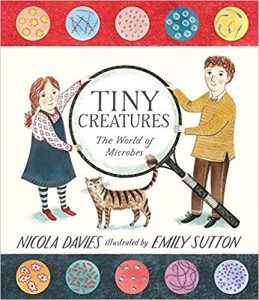 "Book cover, illustration of a boy and a girl holding a huge magnifying glass over the title -- ""Tiny Creatures"""