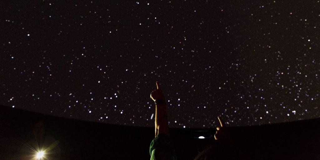 Audience members in a darkened planetarium point upward toward the stars