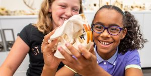 Two smiling girls examine an animal skull that one girl is holding
