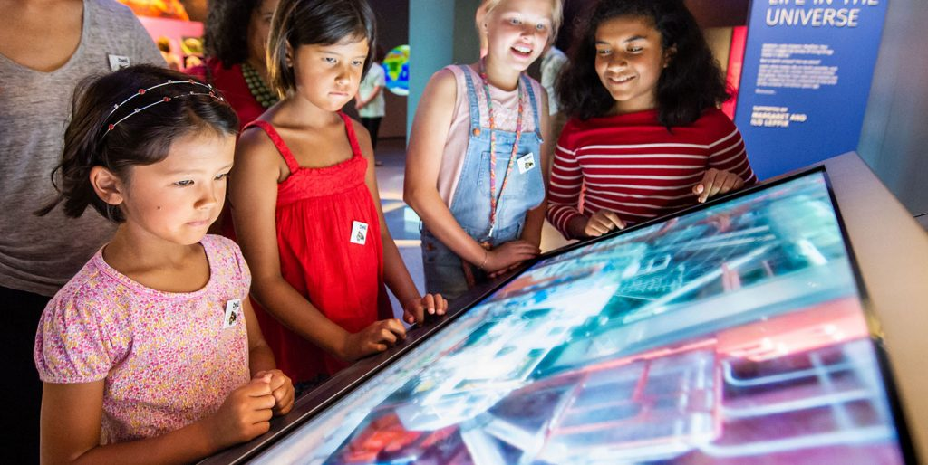 A group of girls explores a museum display highlighting exoplanets