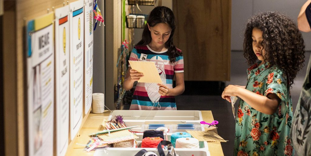 Two girls work with yarn and paper in a weaving project