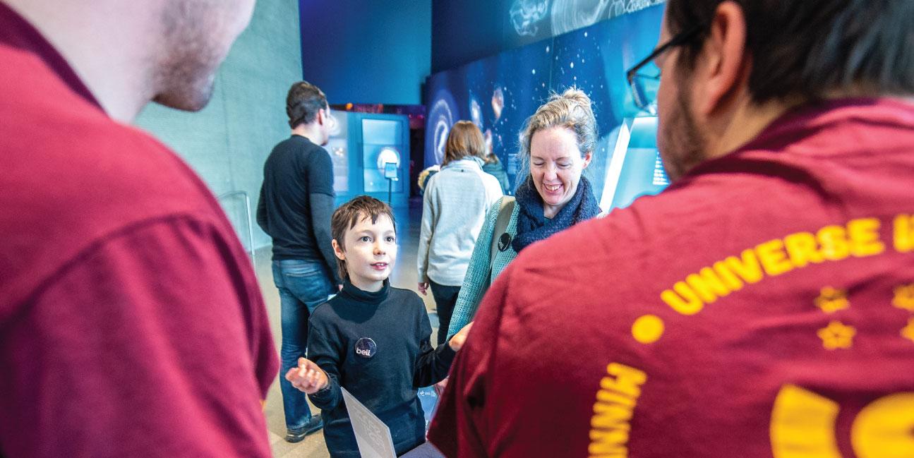 Visitors talk with astrophysics students.