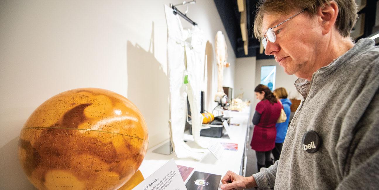 Man looks at a globe of Mars.