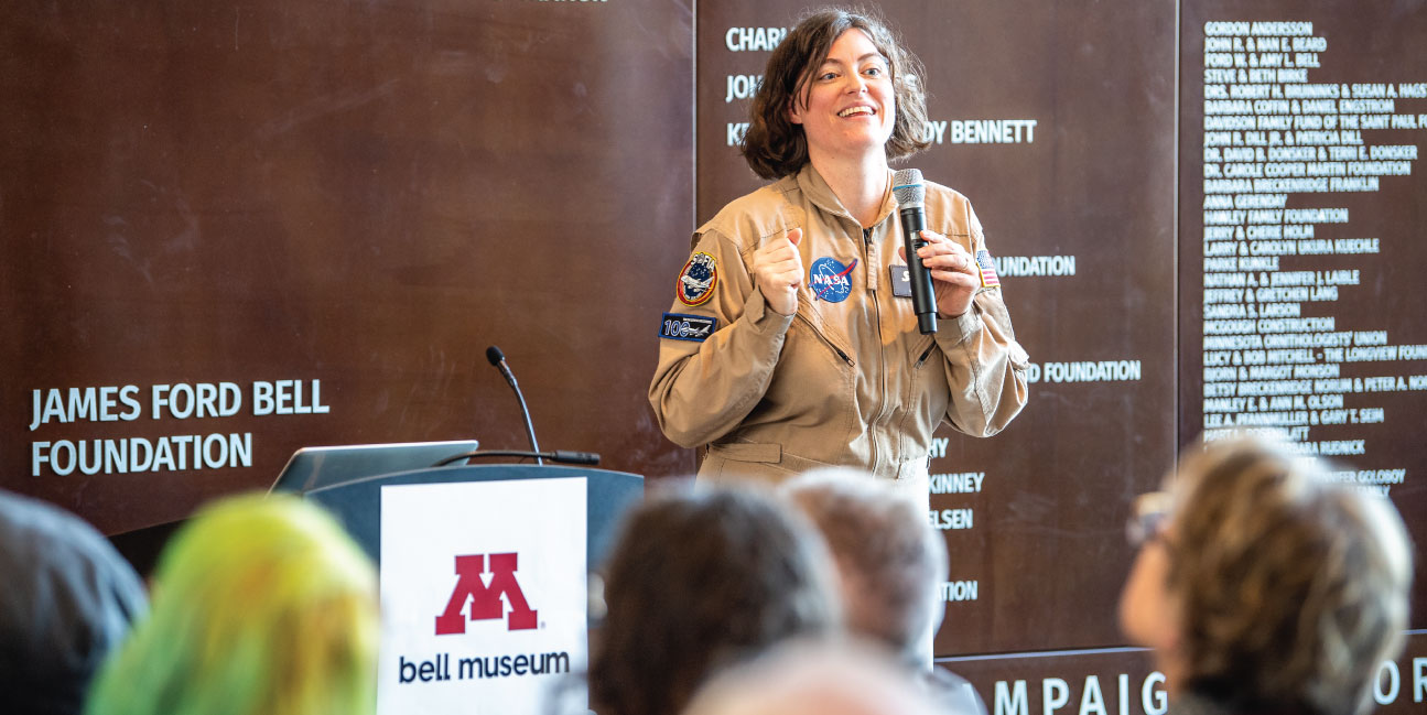 Karina Leppik in full NASA jumpsuit, talks about the her work to a full crowd.