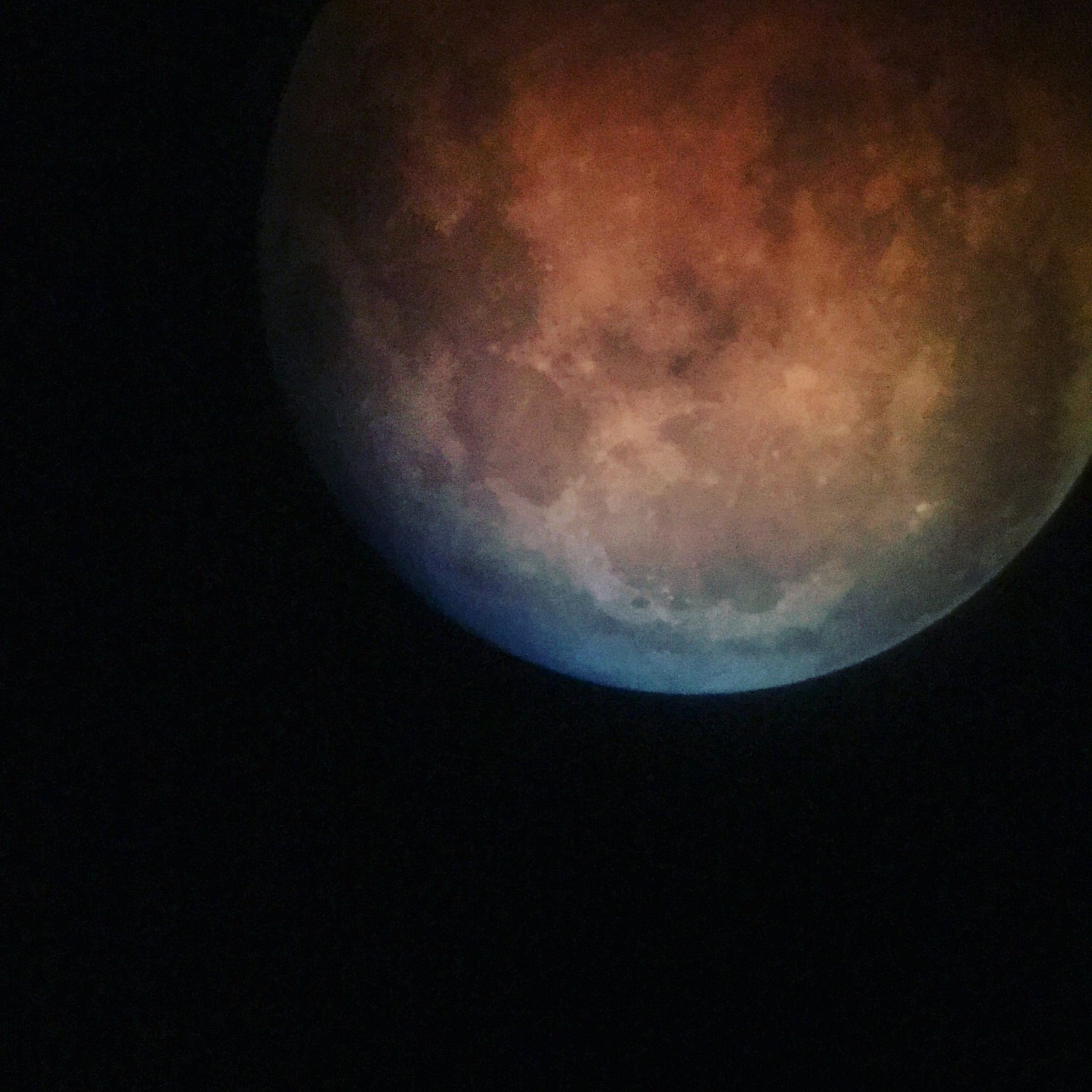The final minutes of totality of the lunar eclipse, a hint of blue grey comes into view as the ruddy color cast by Earth's shadow fades.