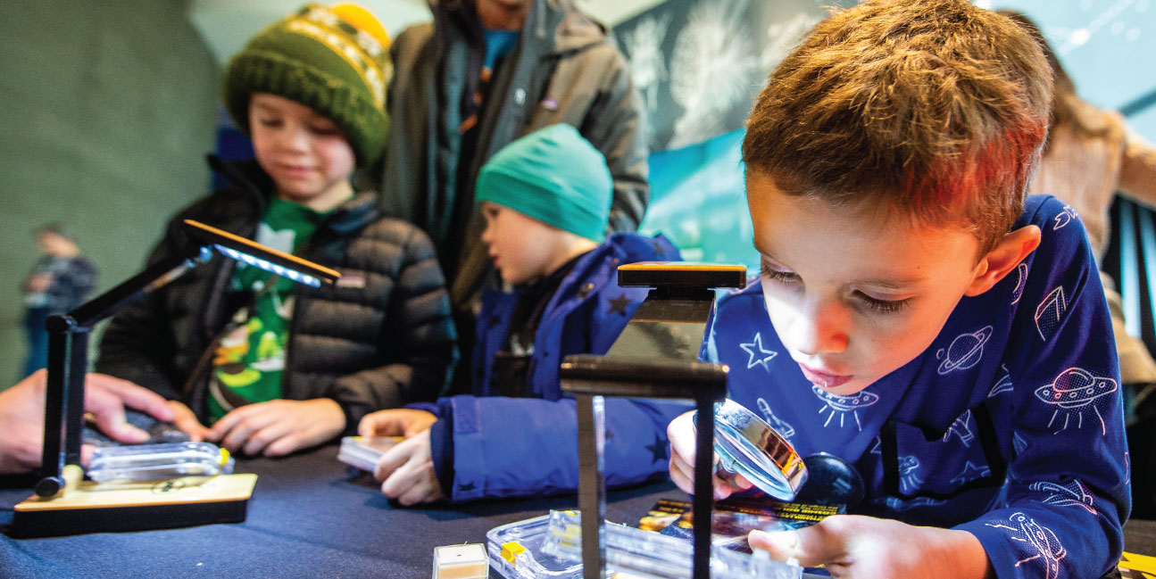 Boy uses magnifier to inspect a meteorite fragment.