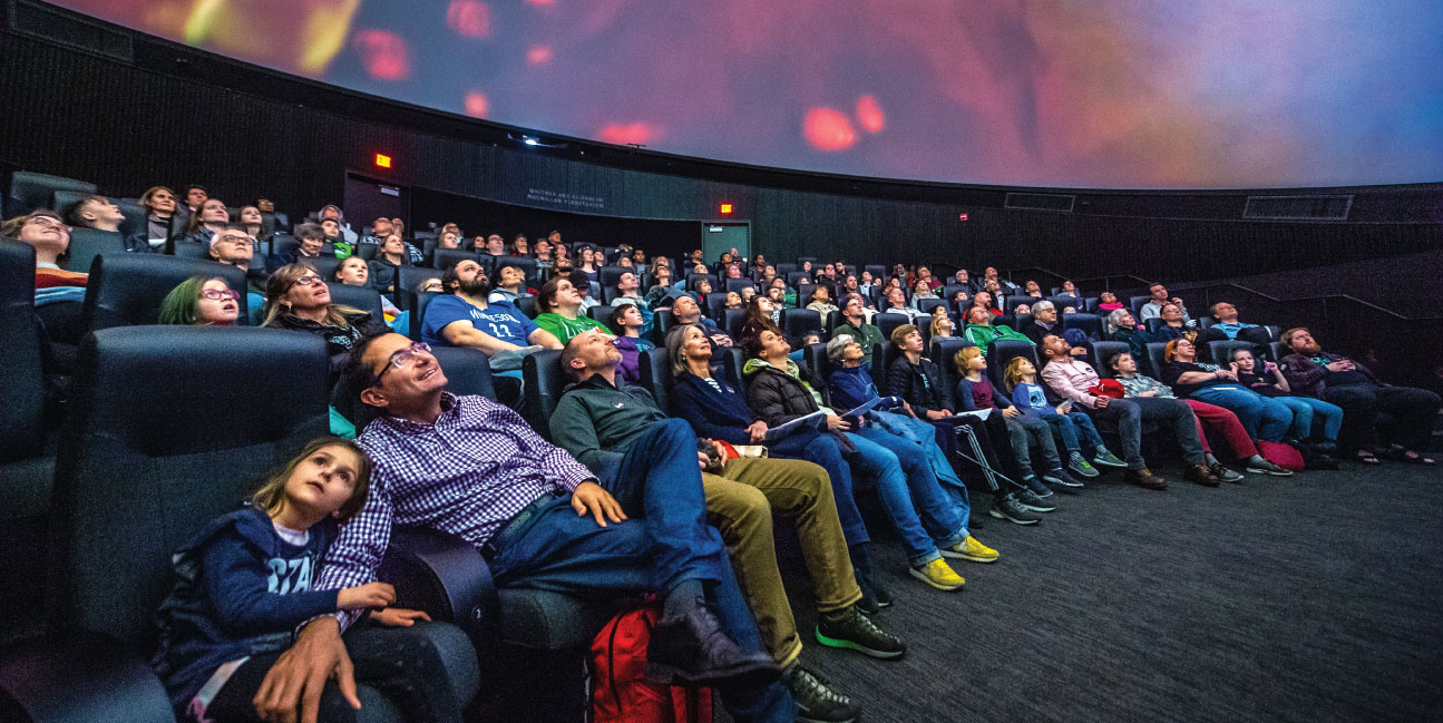 Full theater audience gazing up at a planetarium show.