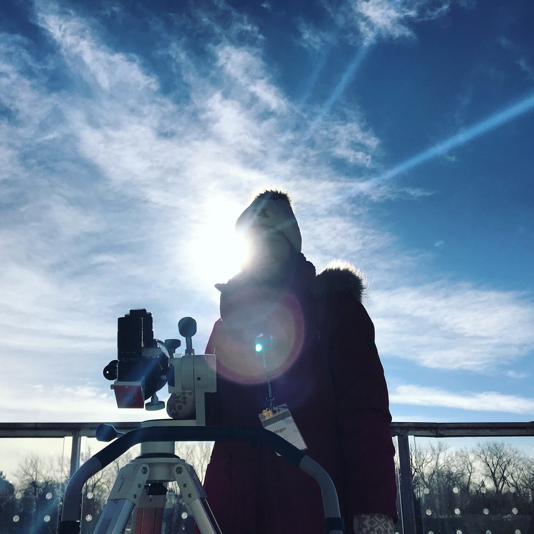 University student standing outside next to a solar telescope.