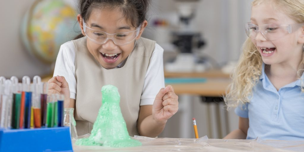 Excited schoolgirls conduct scientific experiment in a beaker, green foam overflowing onto the lab table