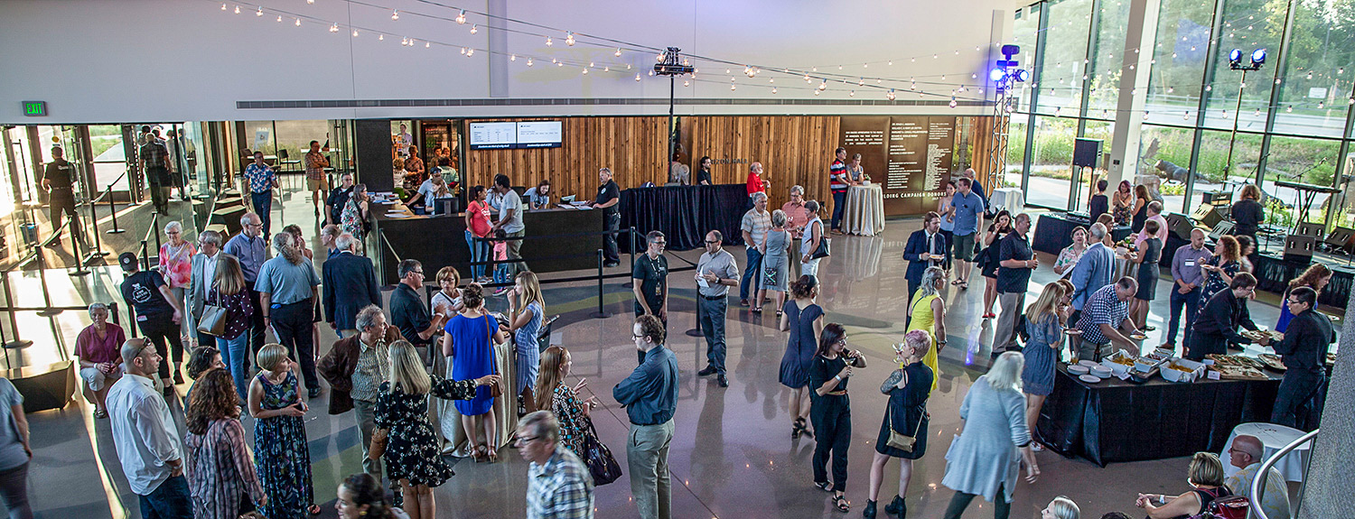 Party with many people standing and also gathering around a buffet table in Horizon Hall