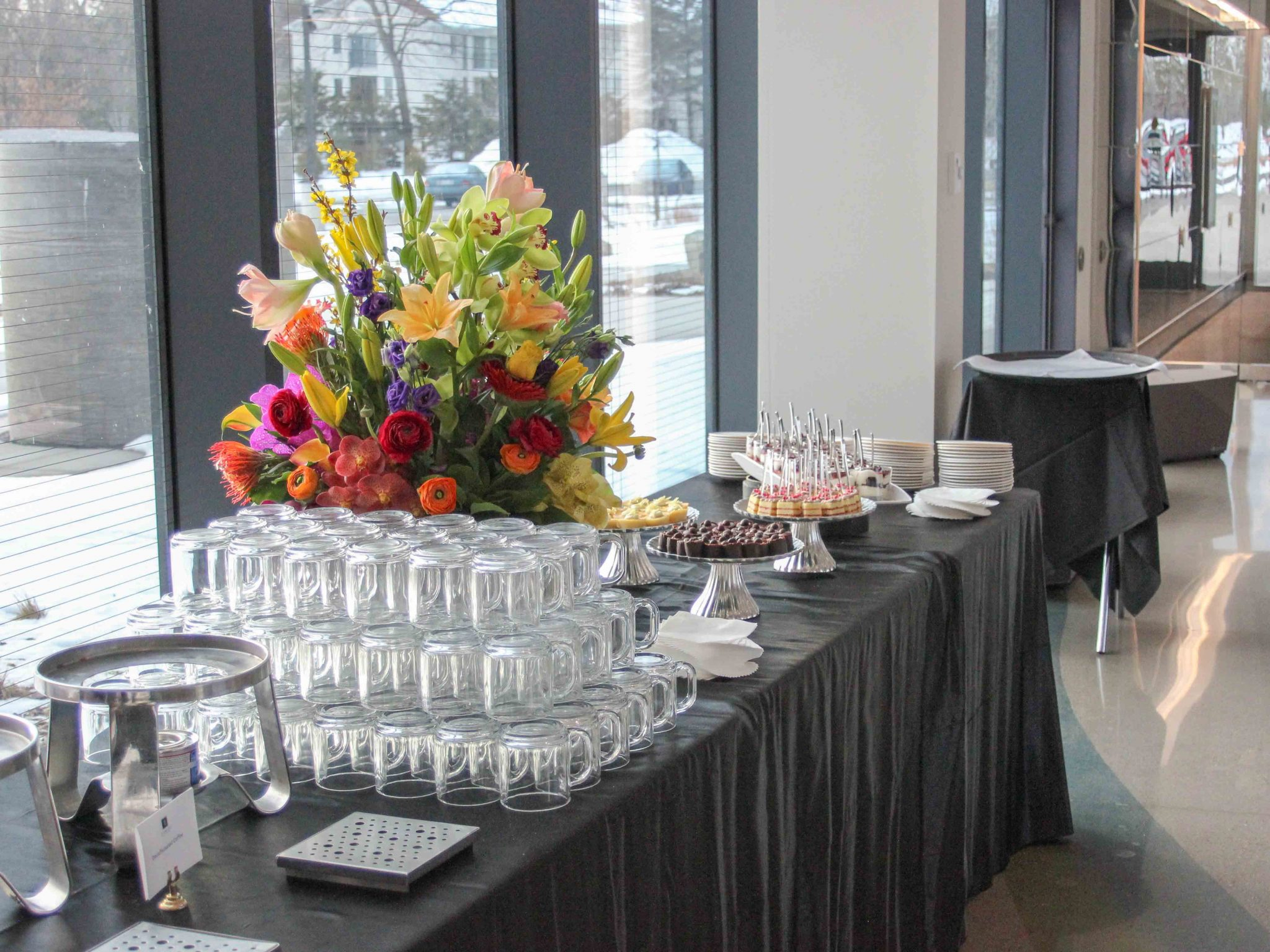Large floral display on dessert buffet table in front of a wall of windows