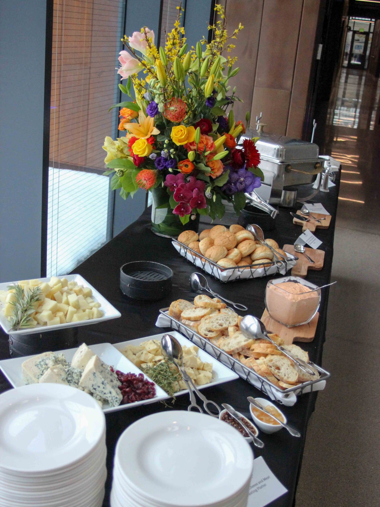 Buffet table with cheese selection, bread, dips