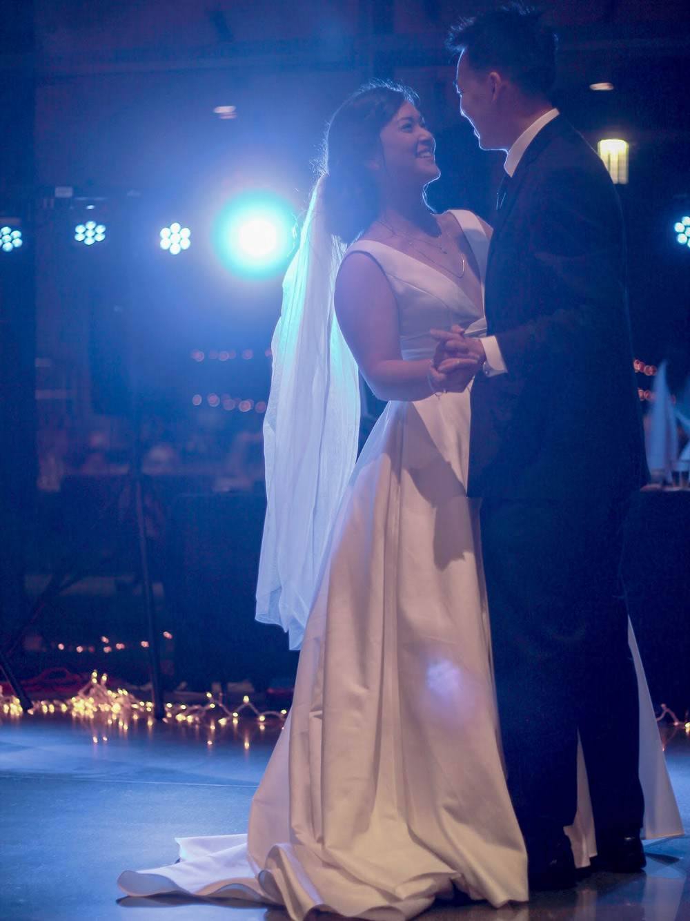 A newly married couple dances with sparkly lights in the background