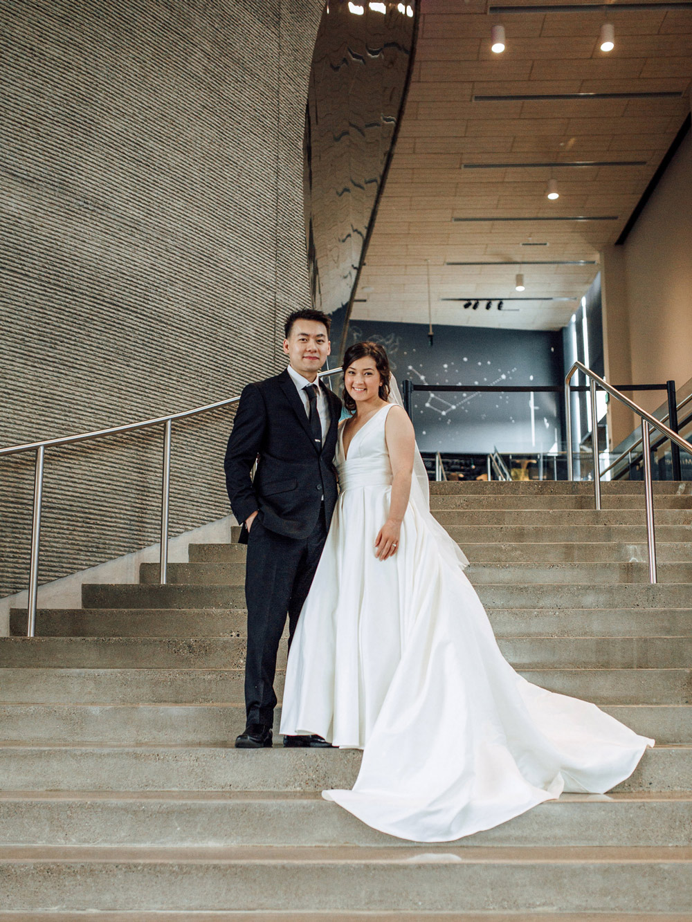 A couple poses on Horizon Hall's grand staircase during their wedding