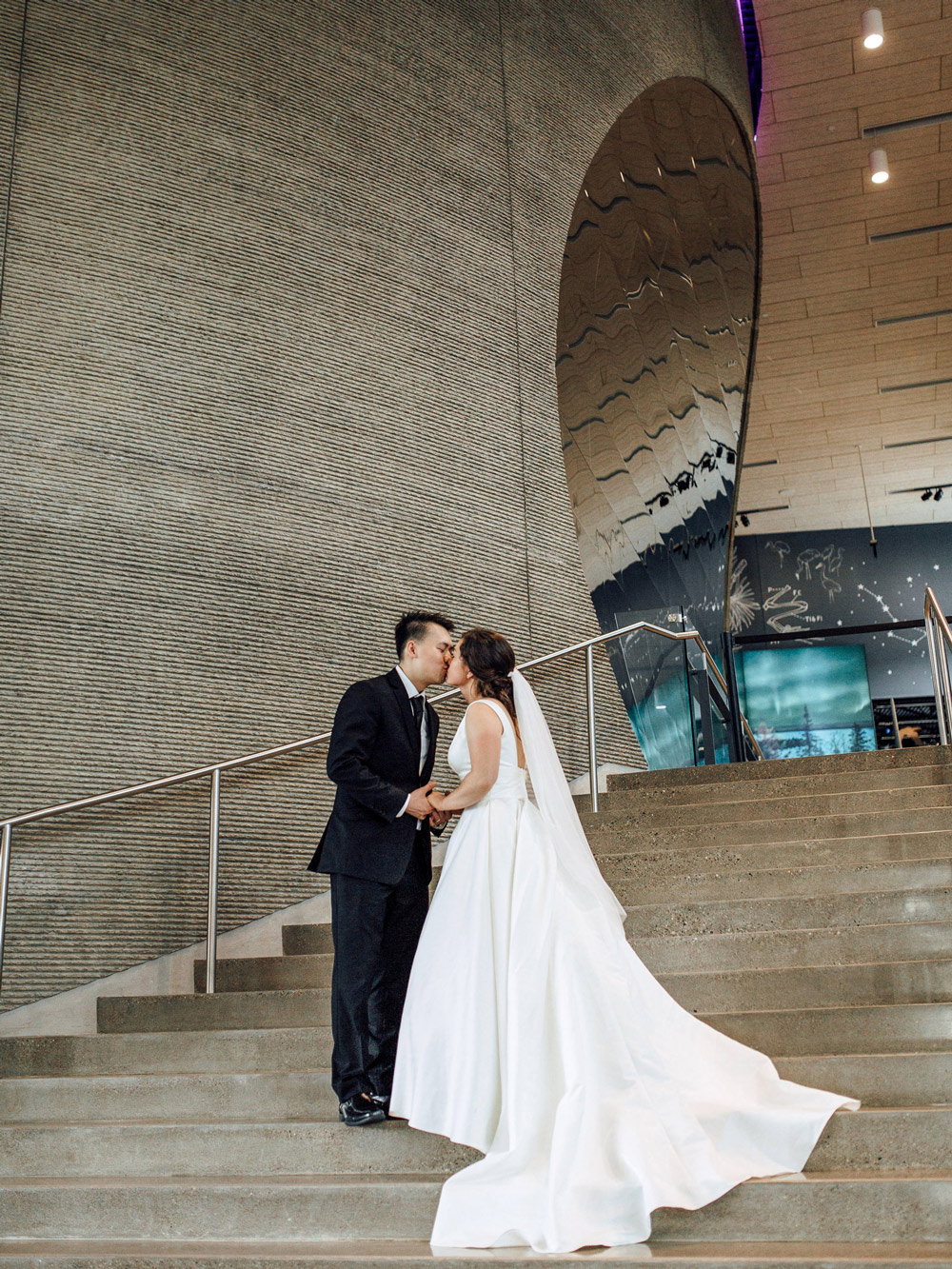A couple kisses on Horizon Hall's grand staircase during their wedding