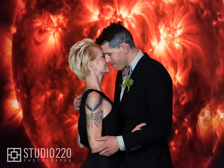 A couple embraces for a wedding photo in front of a large, illuminated image of the Sun's surface