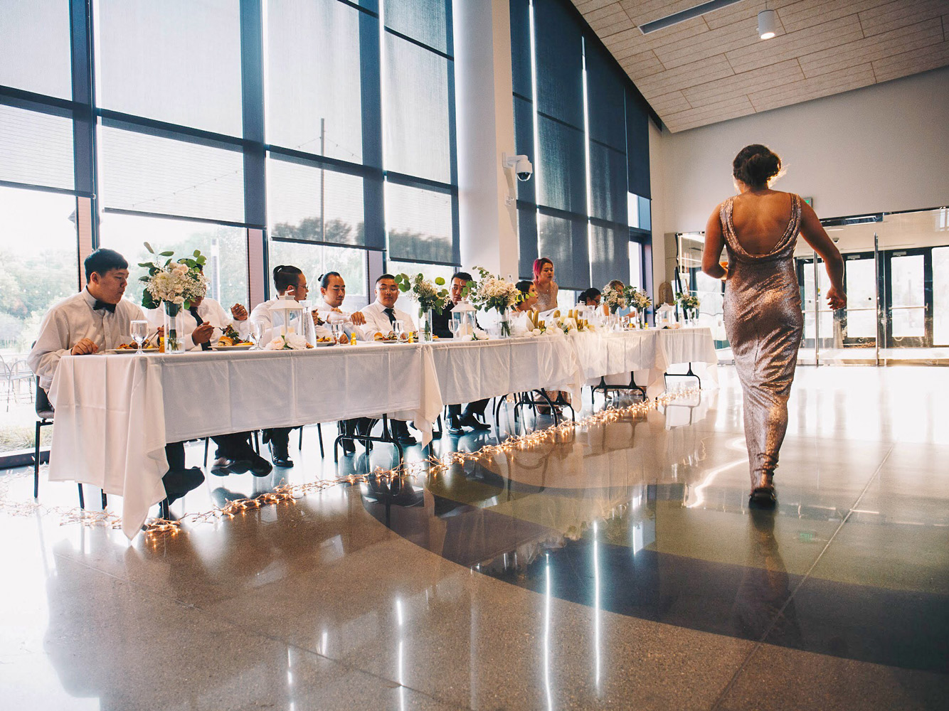 A bridesmaid walks past a wedding party's head table, set with flowers and candles in lanterns