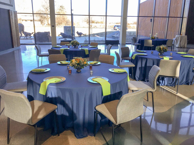 Tables in Horizon hall with table cloths and dinner settings for six