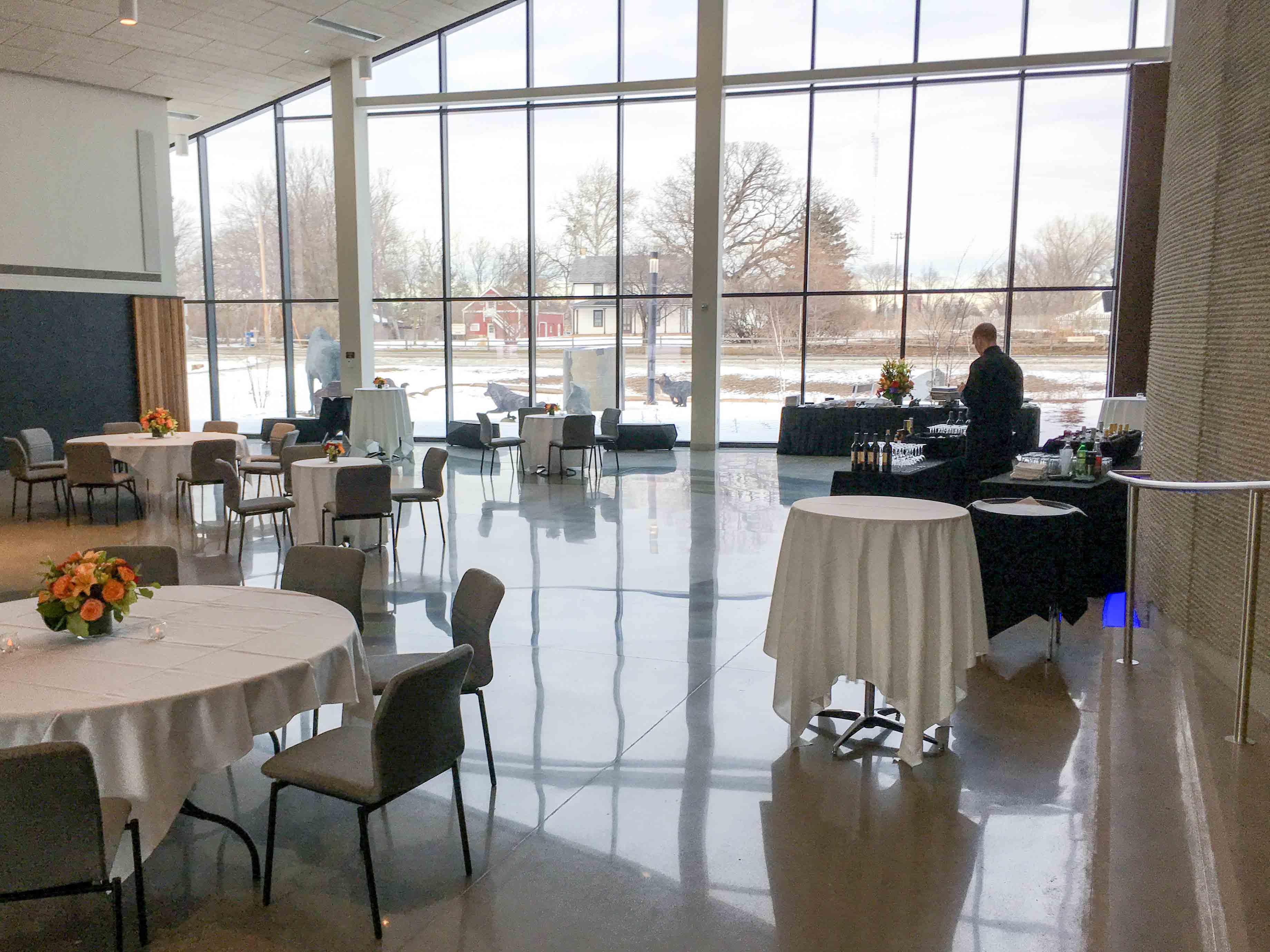 Horizon Hall with tables set for dinner, bar set up, and lots of light streaming in a full wall of windows