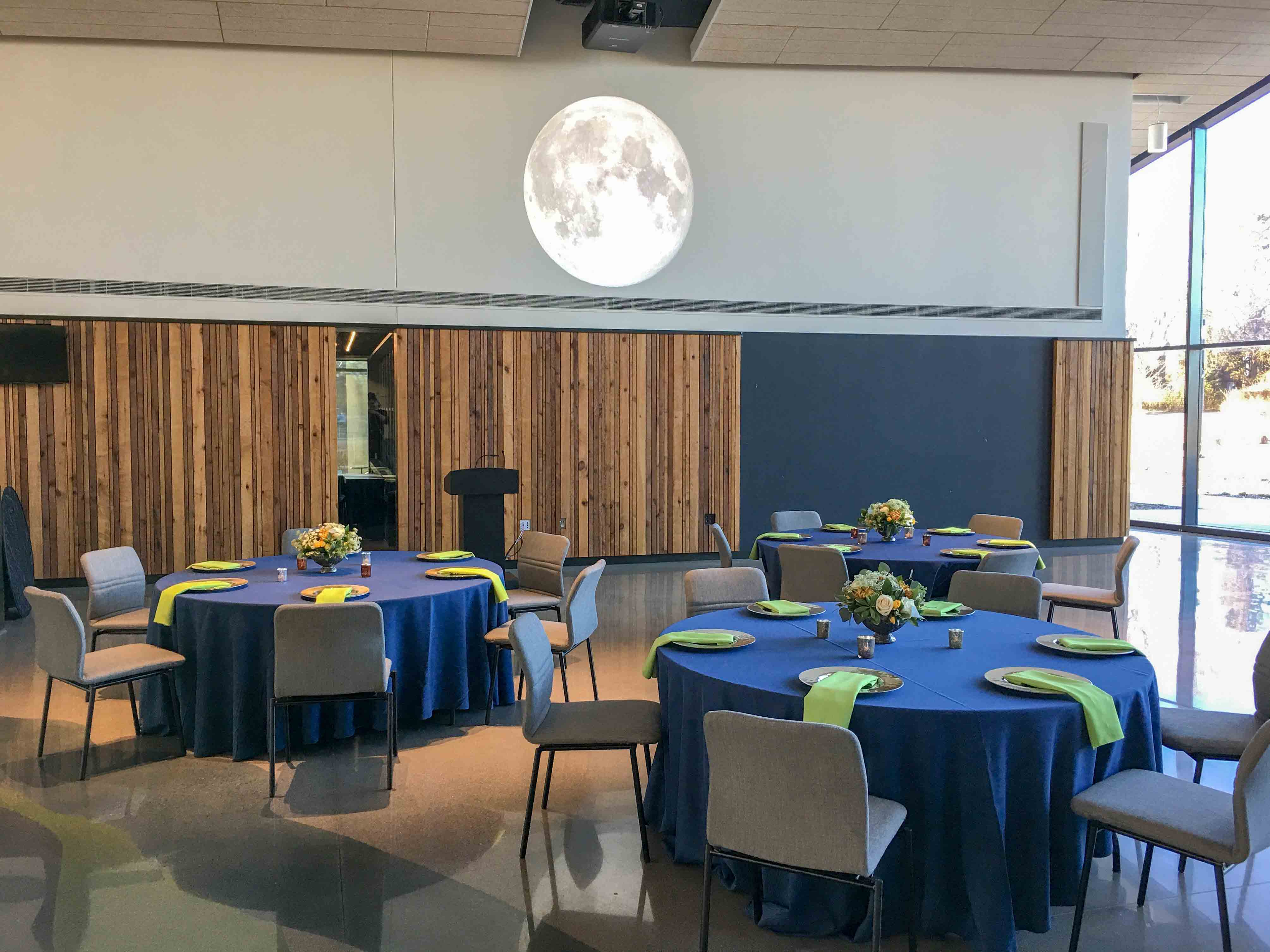 Round tables set for dinner in Horizon Hall, moon image projected onto the wall