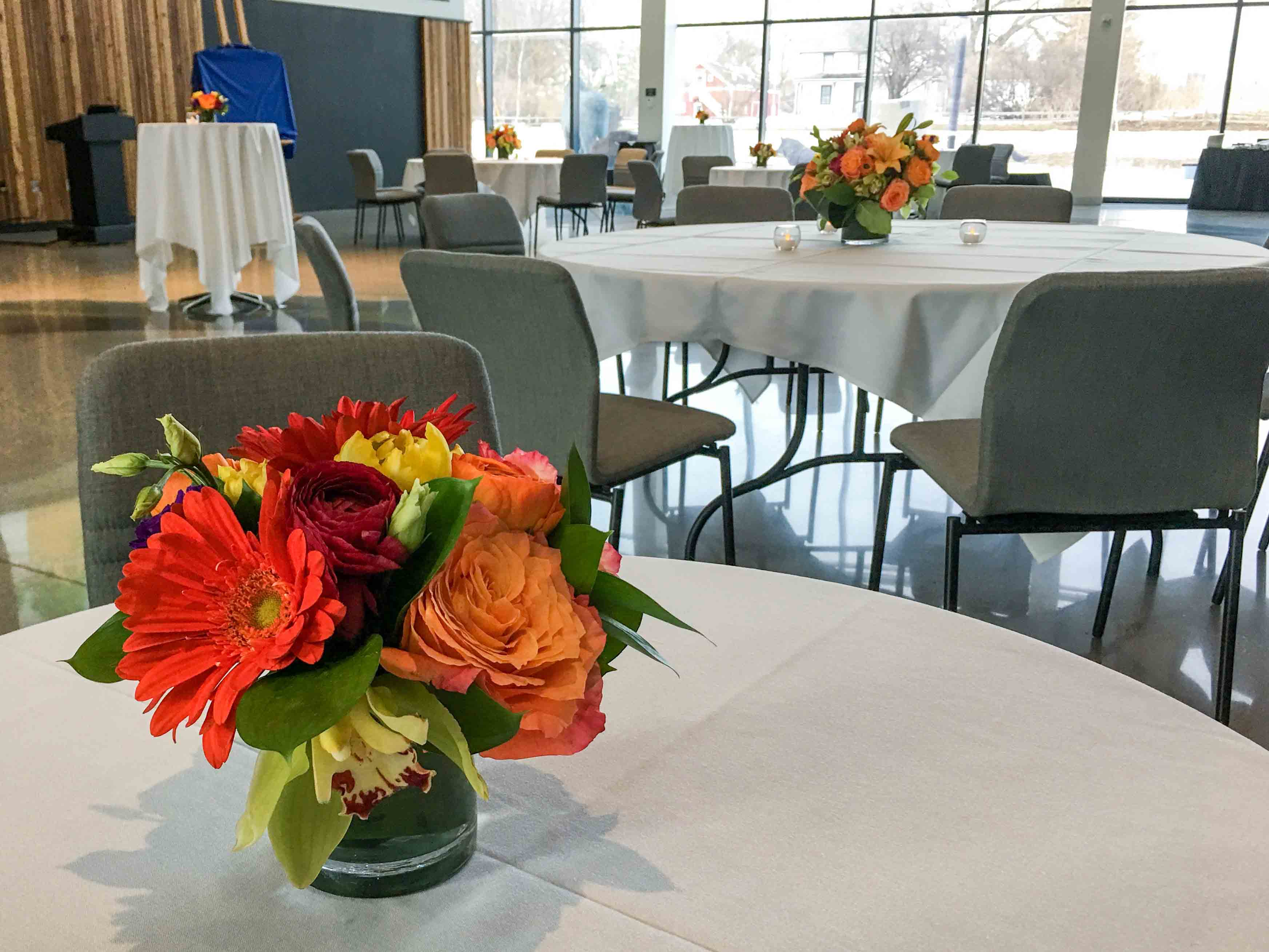 Bright orange, red and yellow flower centerpiece on table with white tableclot