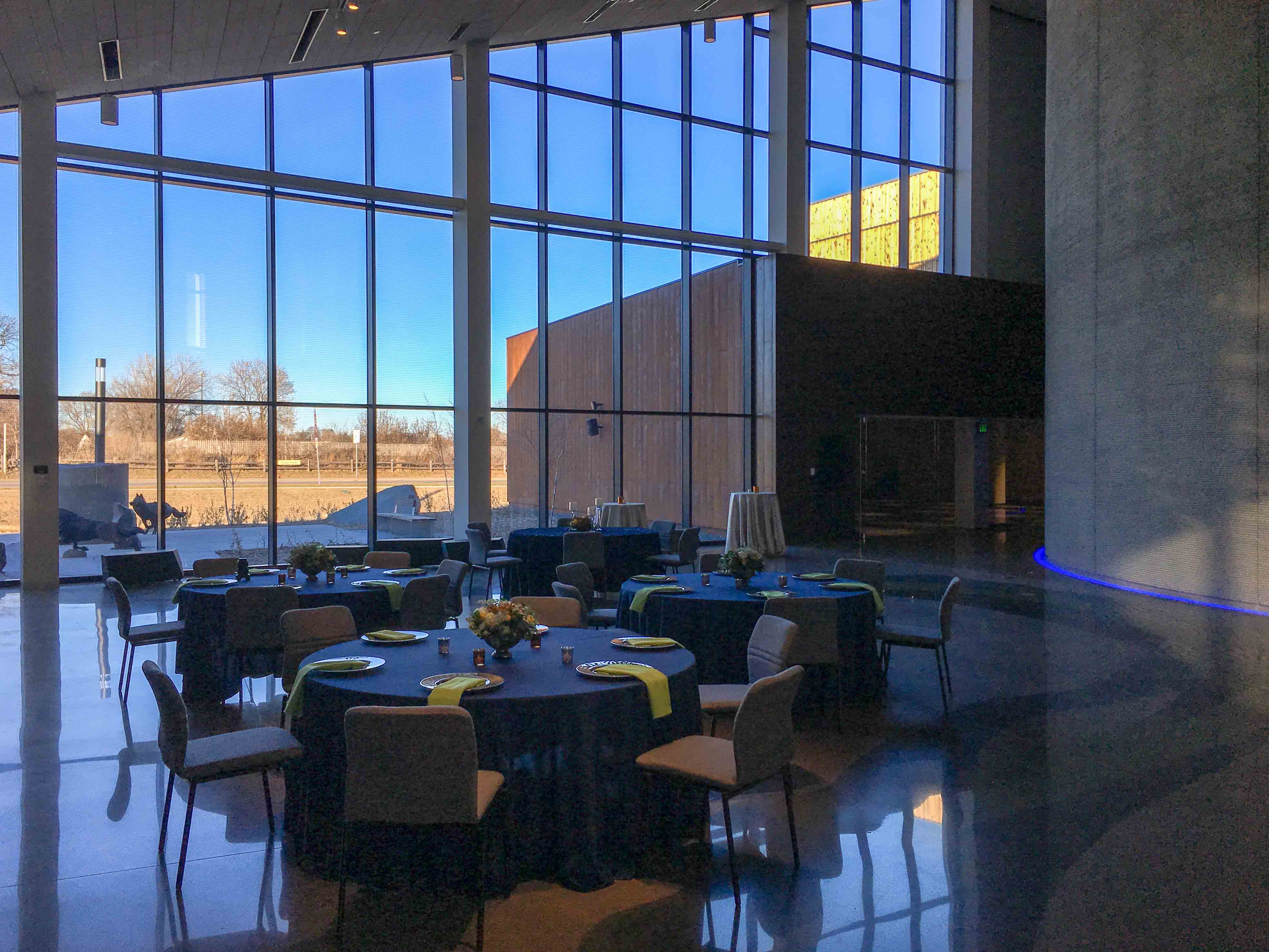 Tables set for dinner in Horizon Hall, blue sky outside tall windows