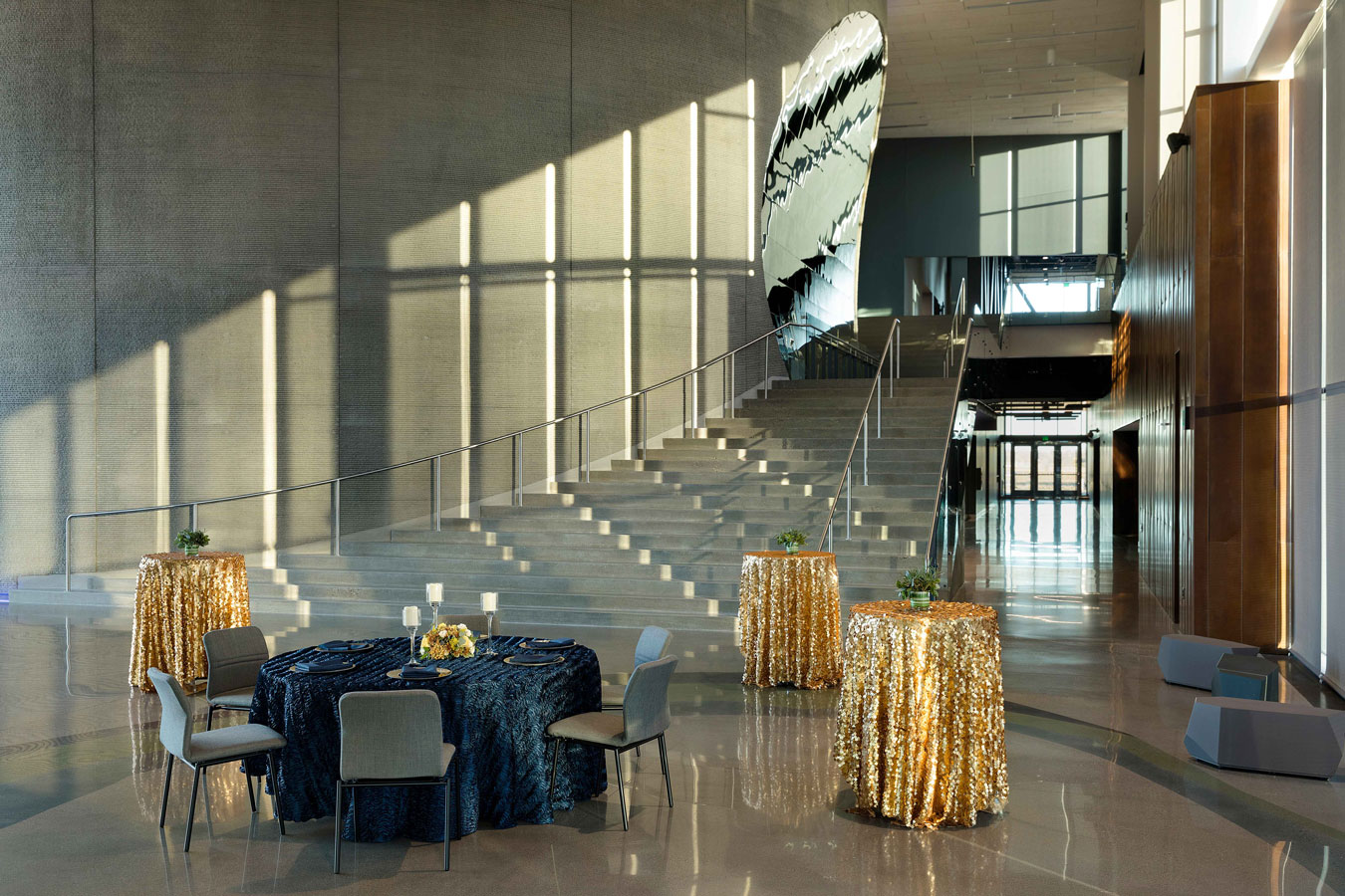 High top tables with sparkly gold table cloths and a round table set for dinner in front of Horizon Hall's grand staircase