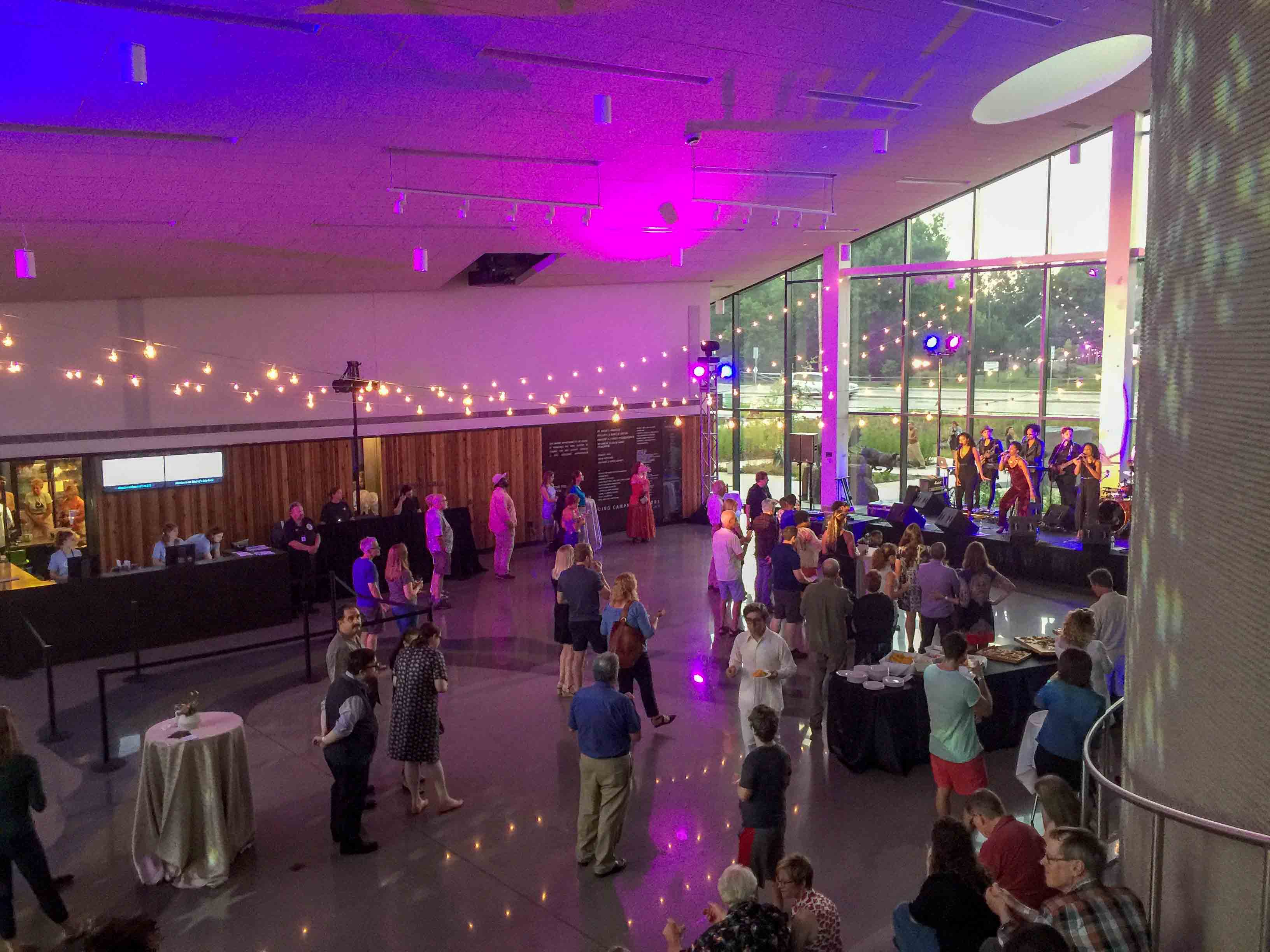 Horizon Hall with strings of cafe lights, purple and blue lights shining on ceiling, and band playing for audience