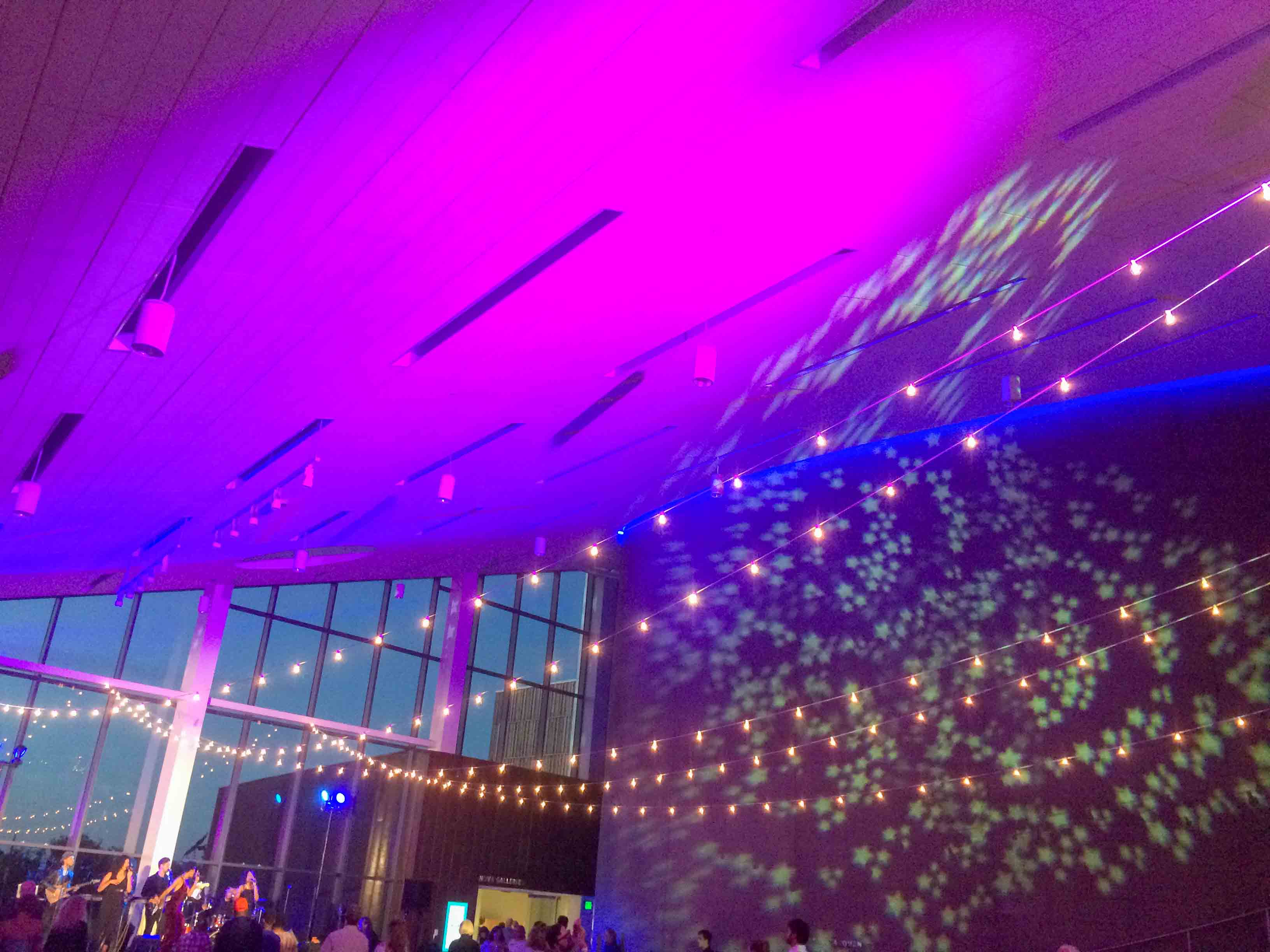 Bright purple and blue lights on Horizon Hall's ceiling, star lights projected onto wall, cafe lights strung across the room