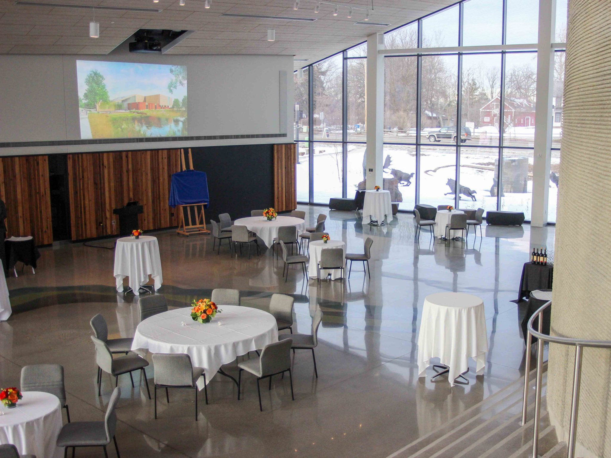 Tables set up for dinner in Horizon Hall, image projected on the wall above the hall