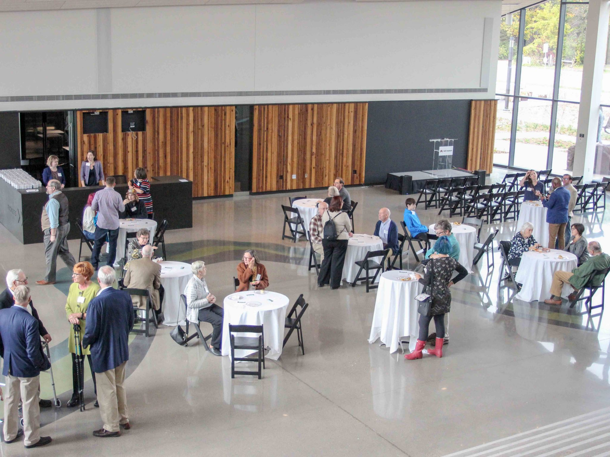 Small lecture setup in Horizon Hall, with people standing and sitting around tables