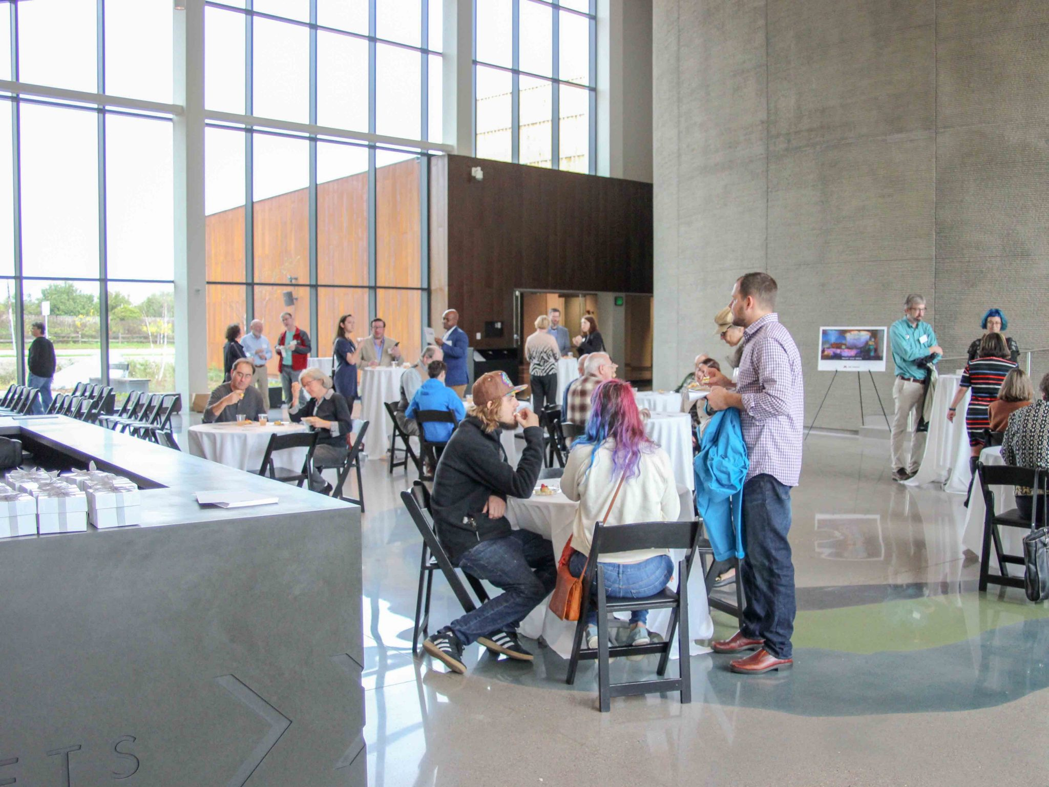 Groups of people chat throughout Horizon Hall, some sitting at tables
