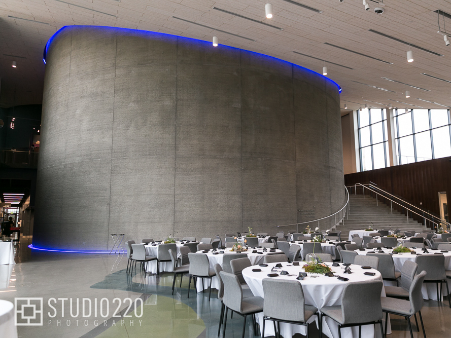 Horizon hall set up for wedding with dinner tables, blue light around the rim of the curved wall