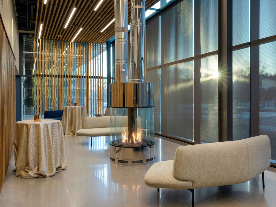 The Bell Museum's lounge, with modern sofas and chairs, fireplace, high top tables with table cloths, floor-to-ceiling windows