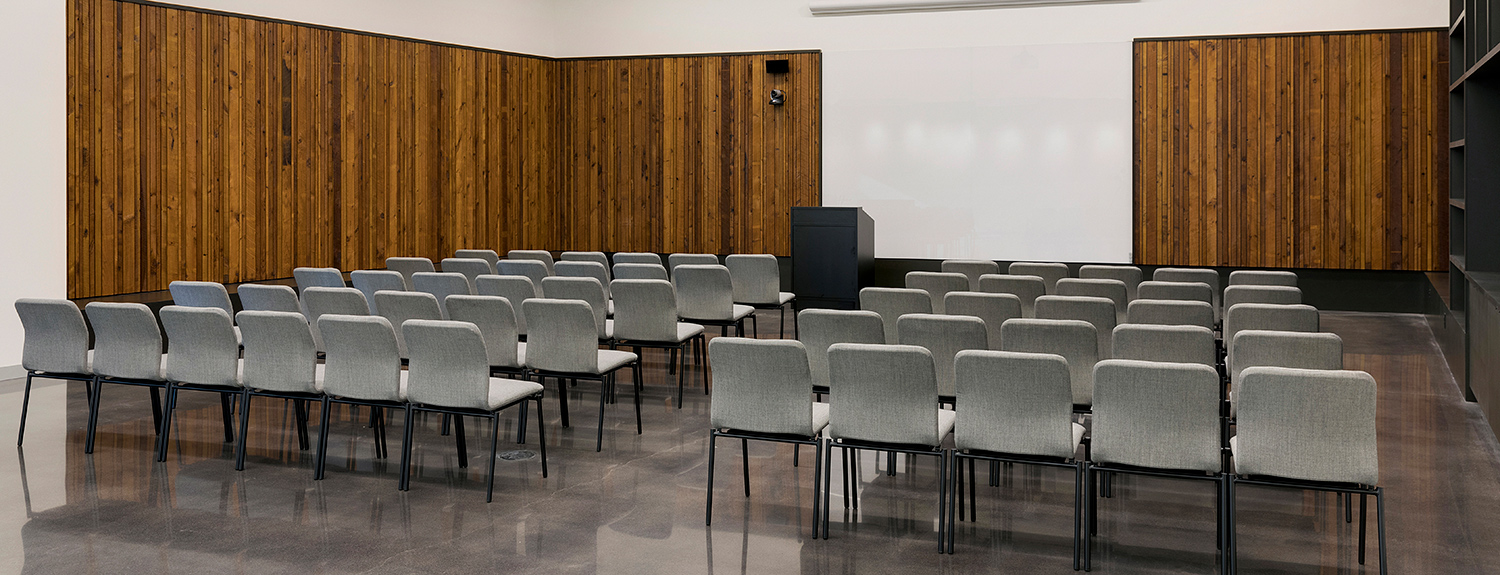 Rows of chairs set up theater style in front of a podium and large white board