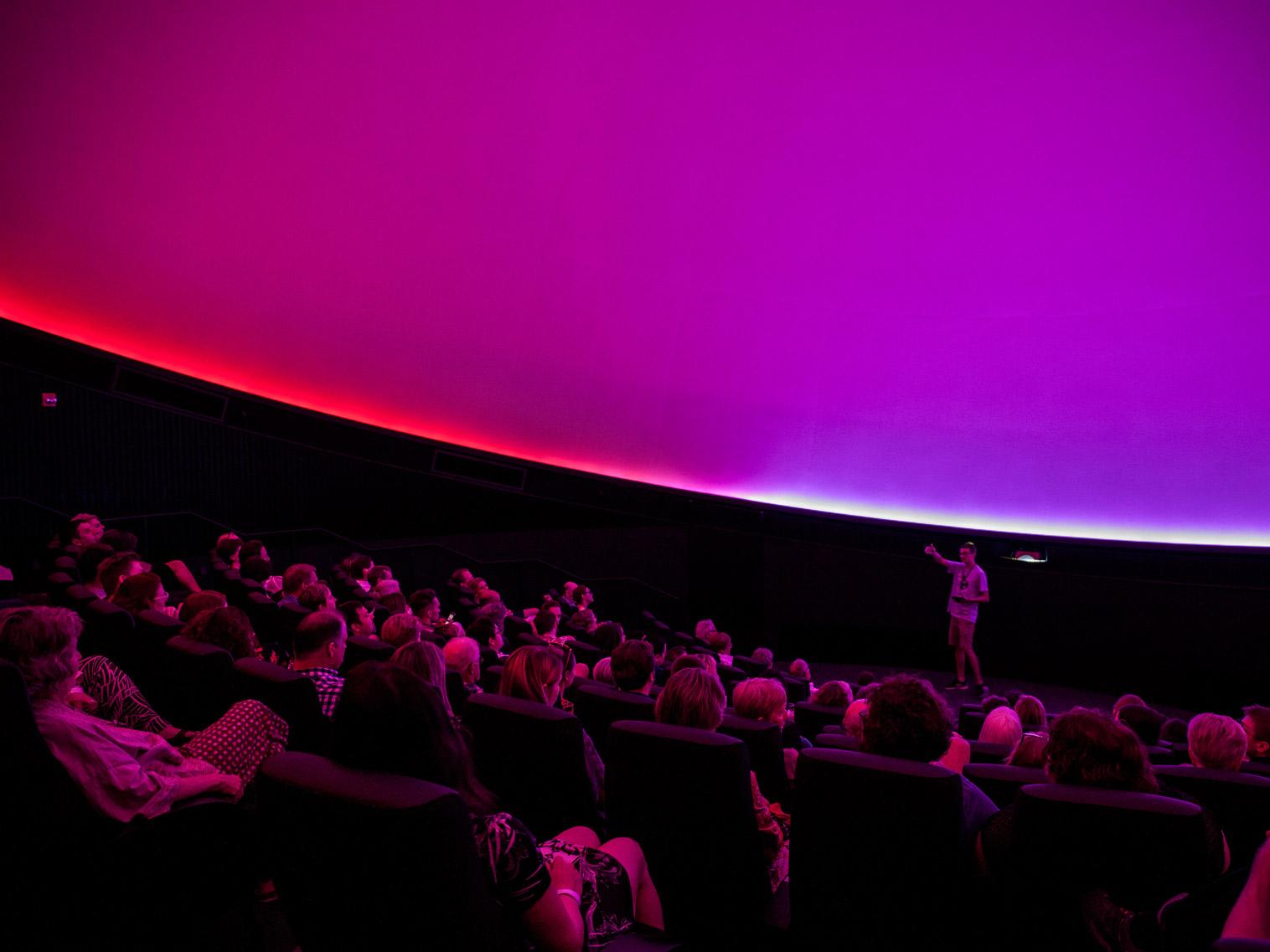 A planetarium audience listens to a presenter under magenta light