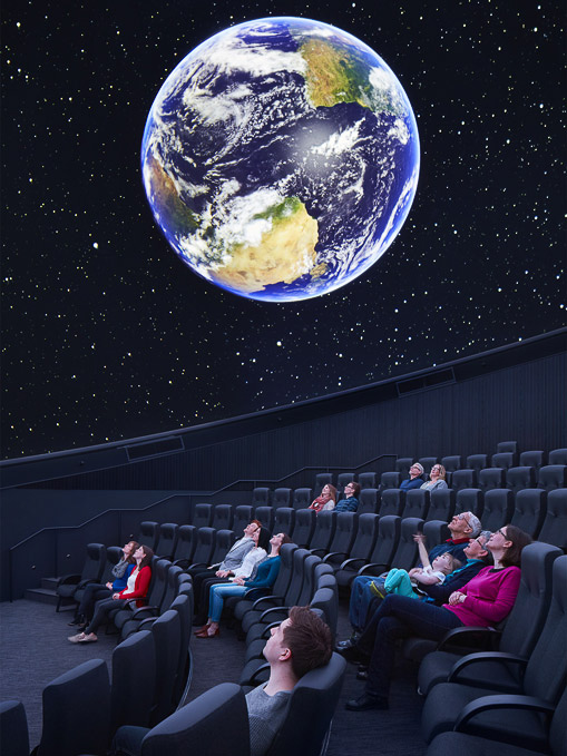 An audience looks at an image of the earth and stars projected on the planetarium screen