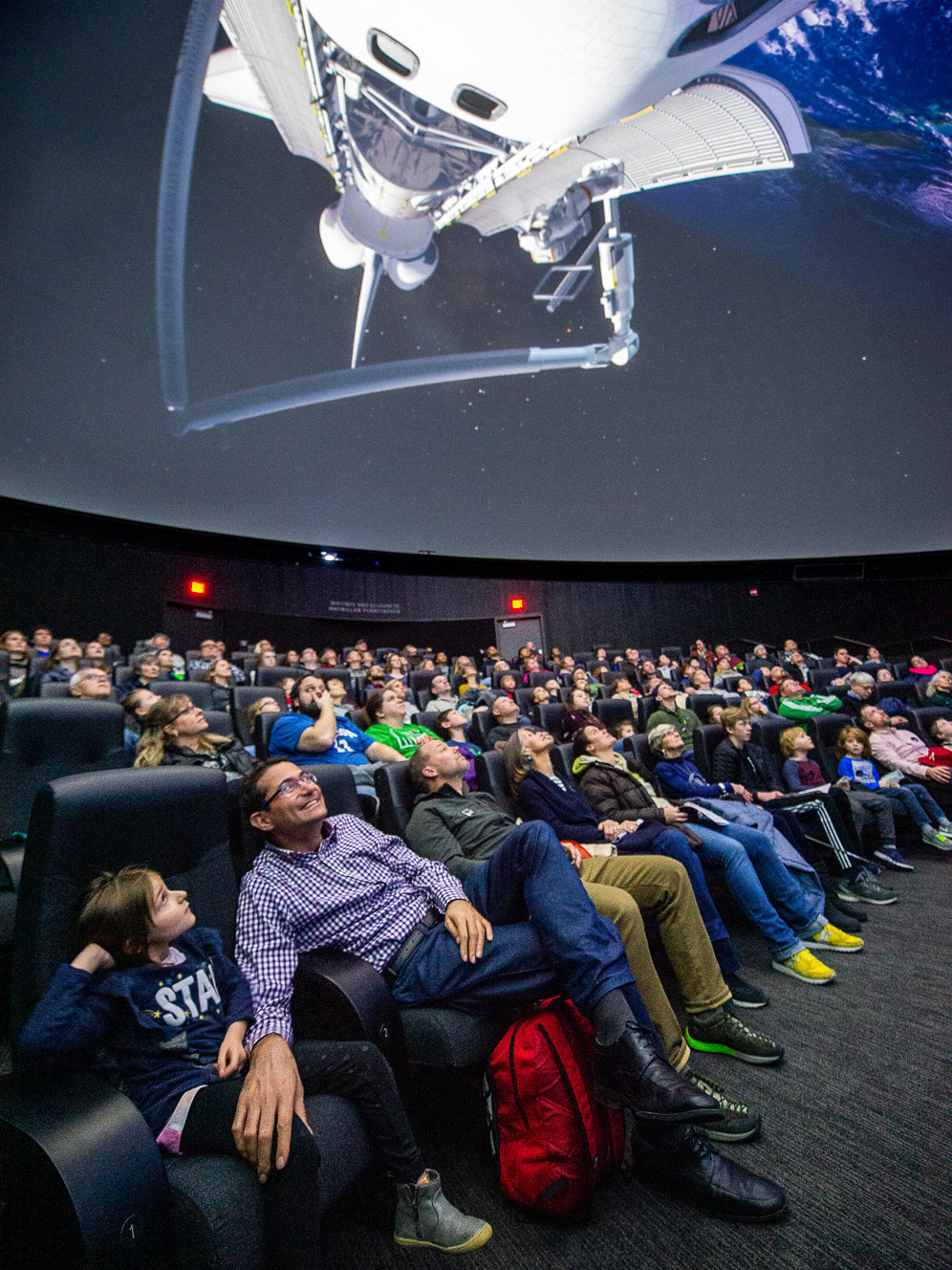 A planetarium audience watches a show