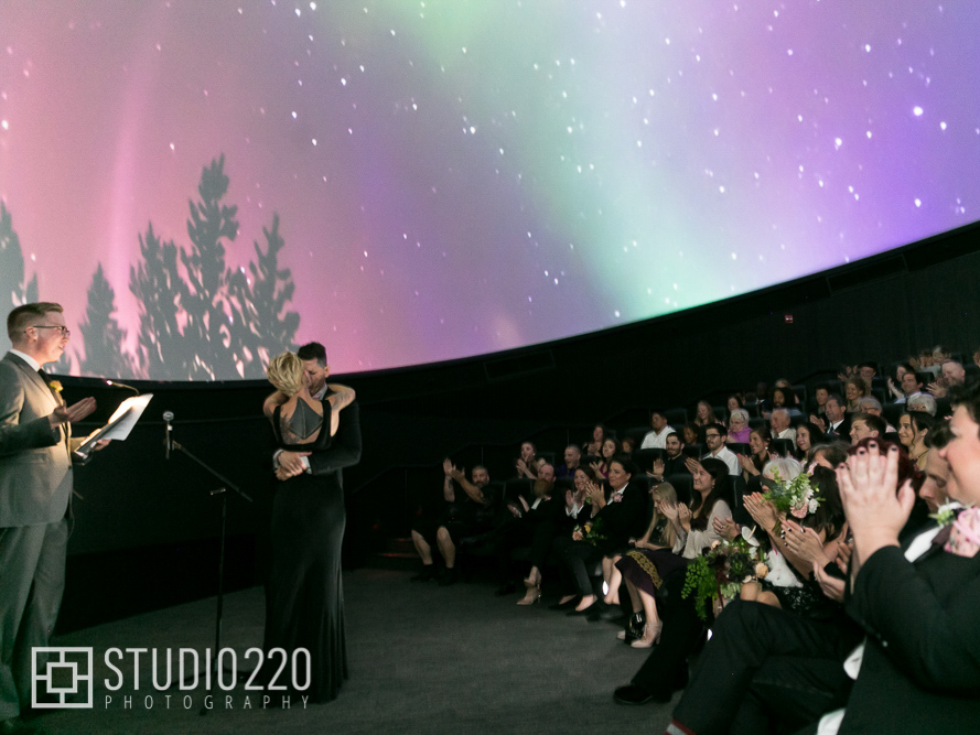 A couple embraces during their wedding ceremony in the planetarium