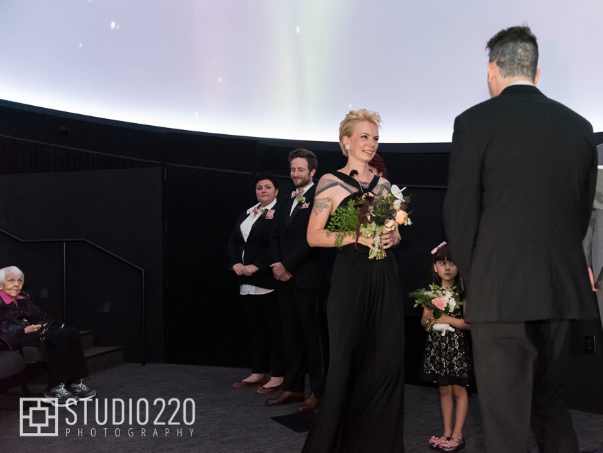 A couple with their wedding attendants during their wedding ceremony in the planetarium