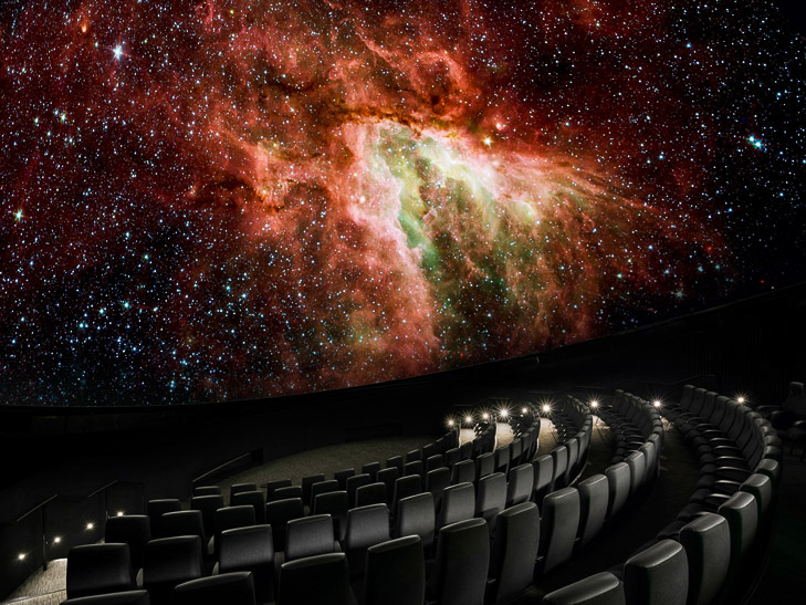 An image of outer space is projected above empty planetarium seats